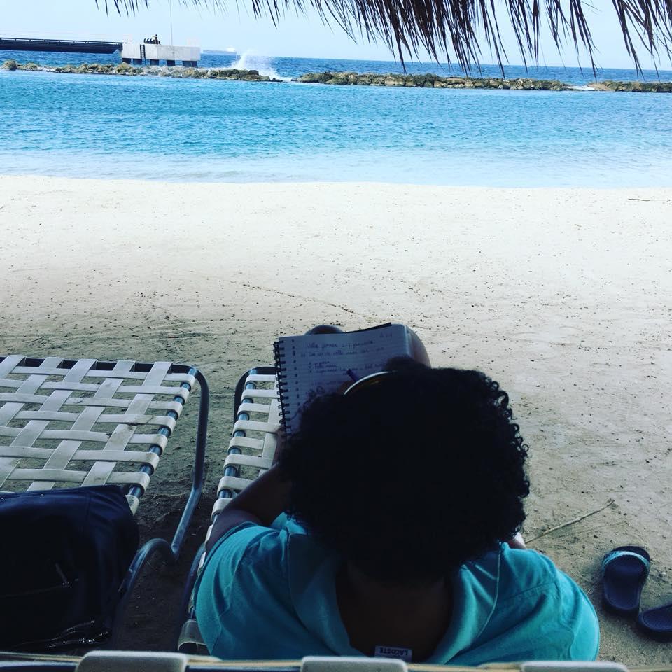 Tibisay Felida met uitzicht naar het strand tijdens het het schrijven van de eerste schrijfronde van De hogepriesteres, roman van Tibisay Felida